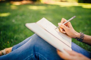 iemand zit in het gras, alleen diens benen zijn zichtbaar. Eén hand houdt een schriftje vast dat op de benen ligt en de andere hand schrijft met een pen in het schrift.