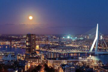 skyline van Rotterdam, waar het eurovisie songfestival gehost werd. De erasmusbrug is te zien en een volle maan