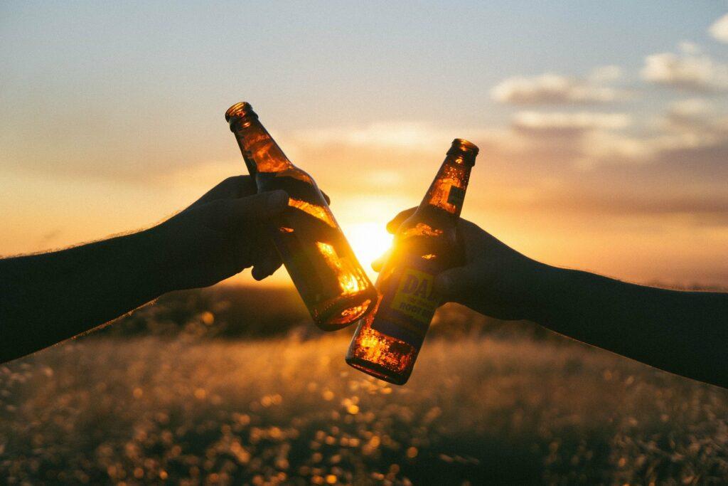 Er worden twee bierflesjes tegen elkaar gehouden door twee handen, op een achtergrond van een ondergaande zon