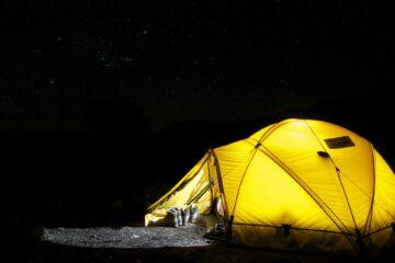 Een van binnen verlichtte gele tent in het donker met sterren in de lucht